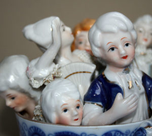 blue white porcelain cup filled with porcelain figurines