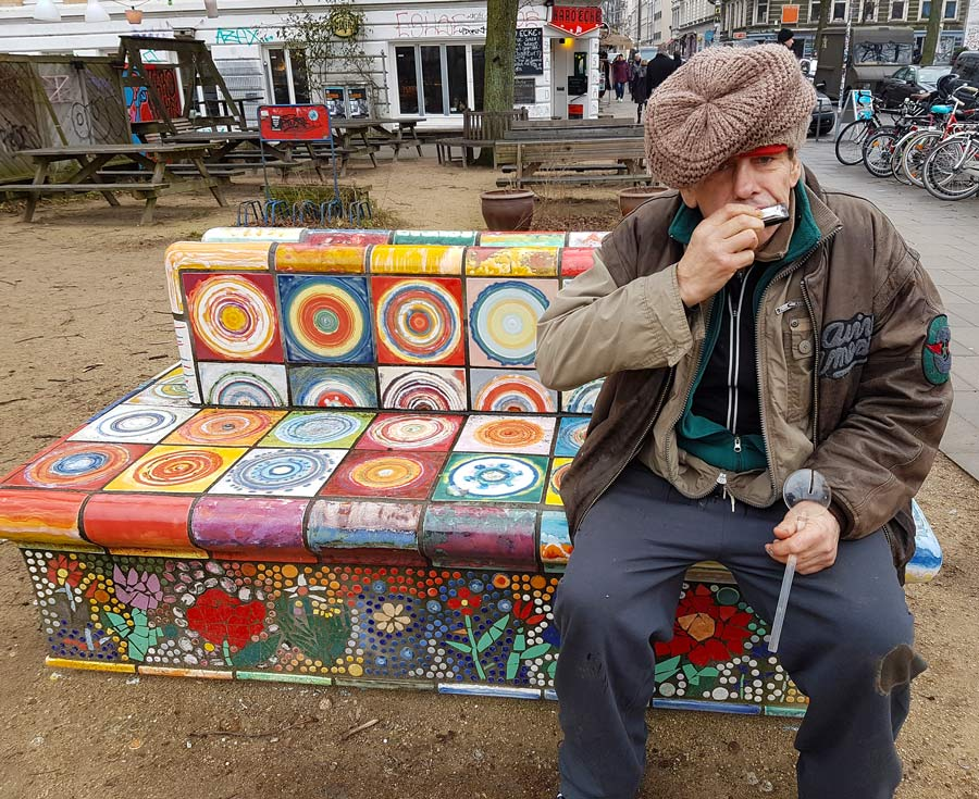 man playing harmonica sitting on ceramic mosaic tiled bench in hamburg