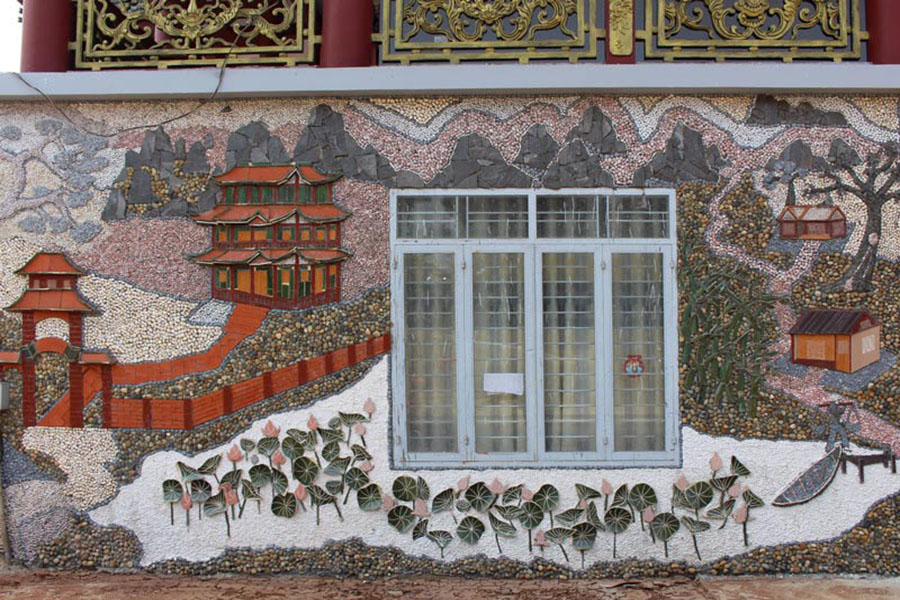 Mosaic mural made with coloured gravel depicting a chinese house mountains and flowers