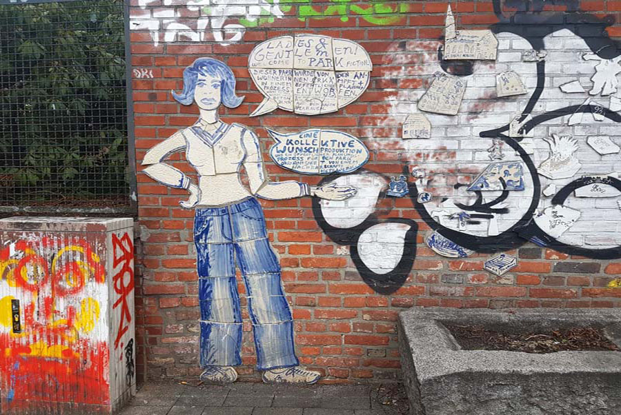 red brick wall showing ceramic street art of a blue and white woman